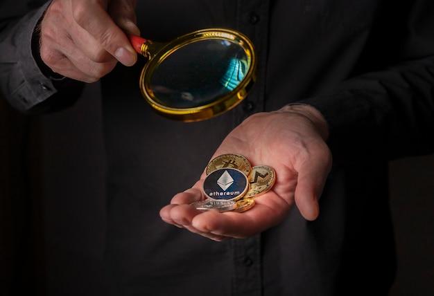 Silber- und goldmünzen der kryptowährung in männlicher handfläche auf schwarzem hintergrund, nahaufnahme. haufen von ethereum, monero, bitcoin und anderen kryptowährungen.
