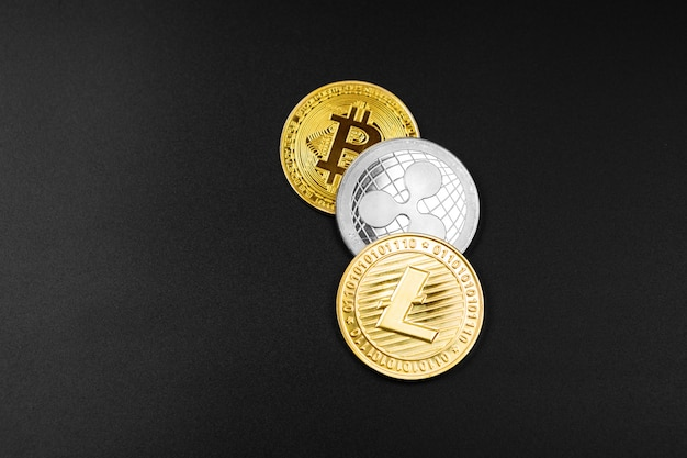 Silber- und goldmünzen mit bitcoin-, kräusel- und äthereumsymbol auf holz.