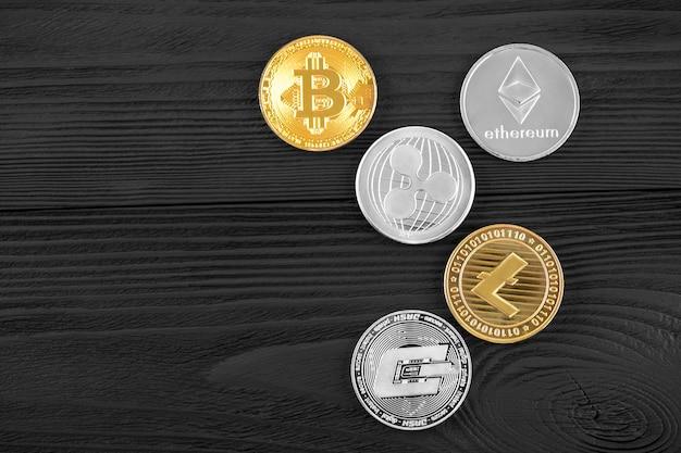 Silber- und goldmünzen mit bitcoin, kräuselung und äthereumsymbol auf hölzernem hintergrund.