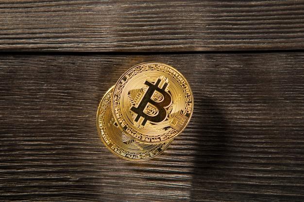 Silber- und goldmünzen mit bitcoin-, wellen- und ethereum-symbol auf holzhintergrund.