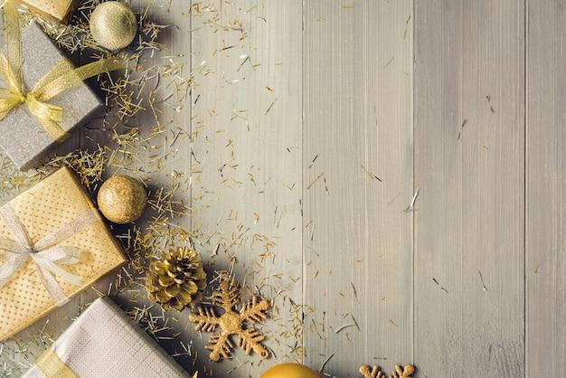Silber- und goldweihnachtsgeschenkboxen und verzierung von einzelteilen auf hölzernem hintergrund