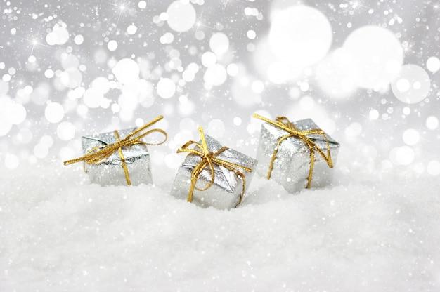 Silber weihnachtsgeschenke im schnee eingebettet