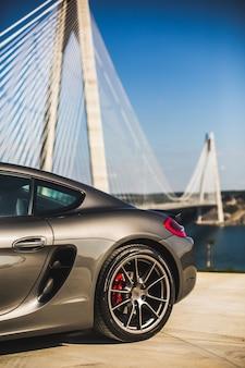 Silberchrom-supersportwagen auf dem außenparkplatz, blick auf die hinterräder