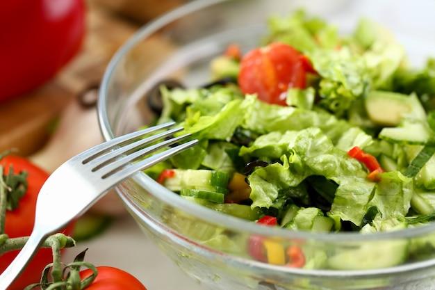 Silbergabel in teller mischt frisches salatgemüse