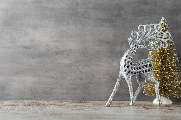 Silberhirsch auf grauem hintergrund. weihnachtshintergrund.