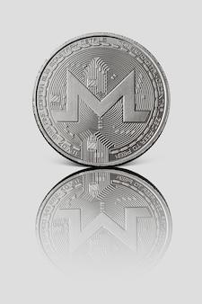 Silbermünze monero mit reflexion auf weißer glänzender oberfläche. konzeptionelles bild für weltweite kryptowährung und digitales zahlungssystem.