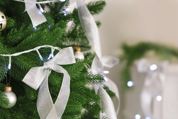 Silberne bänder und weihnachtsbeleuchtung auf tanne im zimmer, nahaufnahme
