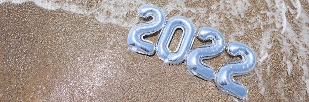 Silberne ballons mit zahlen, die auf sand von meernahaufnahmehintergrund liegen