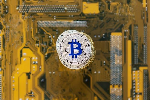 Silberne bitcoin mit reflex auf videokartenhintergrund, draufsicht flach. kryptowährungsbankgeld, online-einnahmen im internet