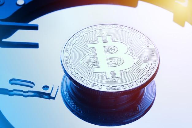 Silberne bitcoin-münze auf der festplattenplatte.