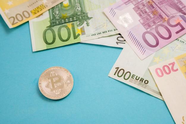 Silberne bitcoin-münze neben euro-banknoten auf blauer oberfläche.