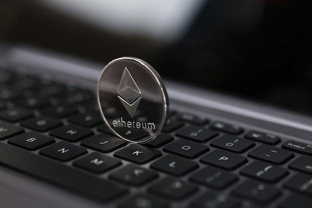 Silberne ethereum-münze liegt auf dem laptop