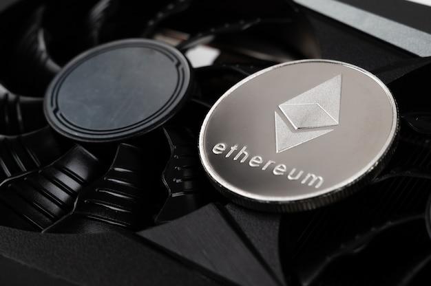 Silberne ethereum-münze liegt auf einer schwarzen grafikkarte. kryptowährung. ethereum-mining-konzept.