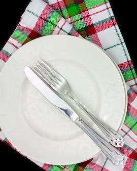 Silberne gabel und messer auf weißer platte mit mustern auf karierten tuch weihnachtsfarben