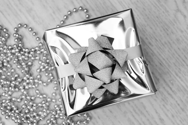 Silberne geschenkbox auf einer draufsicht des hölzernen hintergrundes. weihnachtsferien-konzept. flach liegen.