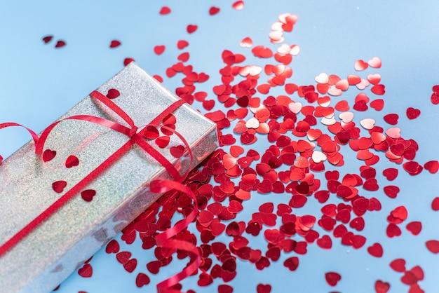Silberne geschenkbox zum valentinstag mit rotem herzförmigem glitzer