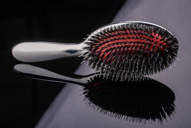 Silberne haarbürste mit roter mitte und hochwertigen mehrschichtigen zähnen auf reflektierendem schwarzem hintergrund