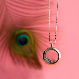 Silberne halskette für dame, die auf pfauenfeder glänzt. luxuriöse silberschmuckketten mit glas und kristallen. kleines schönes geschenk aus edelmetall für die frau. luxusschmuckgeschenk auf rosa hintergrund