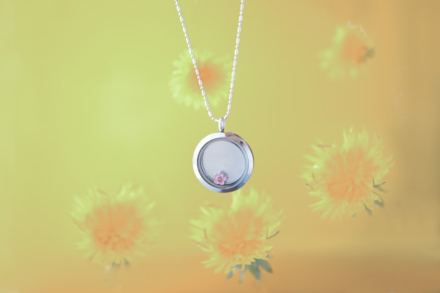 Silberne halskette für sie, die auf gelbem hintergrund mit löwenzahn glänzt. luxuriöse silberschmuckketten mit glas und kristallen. kleines schönes geschenk aus edelmetall für die frau. luxus-ausdrücke