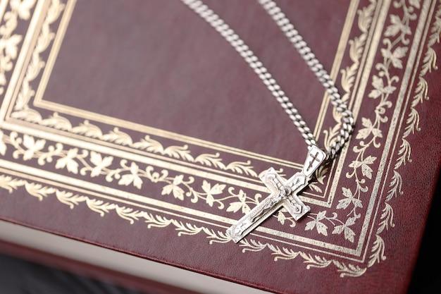 Silberne halskette mit kruzifixkreuz auf christlichem bibelbuch auf schwarzem holztisch.