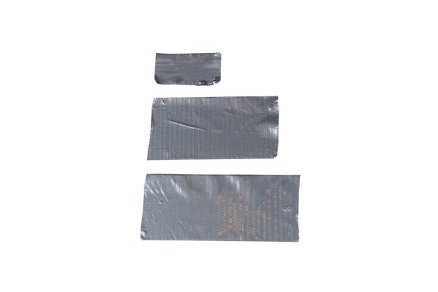 Silberne klebebandstücke lokalisiert auf weißem hintergrund. draufsicht.