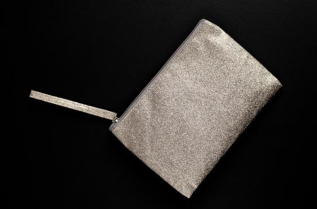Silberne kosmetiktasche auf schwarzem