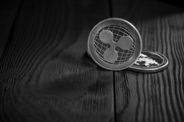 Silberne kräuselungsmünzen auf schwarzem holz