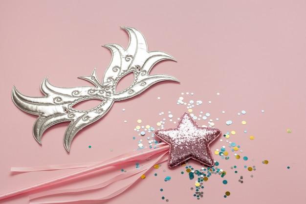 Silberne maske mit rosa stern auf stab