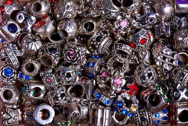 Silberne perlen von verschiedenen formen mit farbiger steinnahaufnahme.
