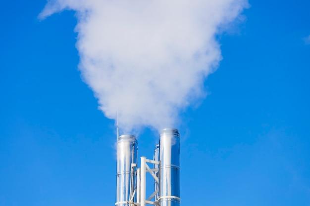 Silberne pfeifen, aus denen rauch aufsteigt. heizraum arbeiten. foto in hoher qualität