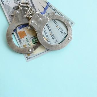 Silberne polizeihandschellen und hundert dollarscheine liegen auf hellblauem hintergrund