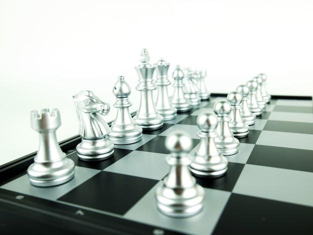 Silberne schachfiguren an bord für spielanfang, intellektuellen sport und taktisches spiel