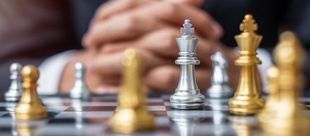Silberne schachkönigfigur gegen torschachbrettgegner mit geschäftsmannmanagerhintergrund.