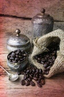 Silberne schale und kaffeebohnen in der sackleinentasche auf hölzernem hintergrund