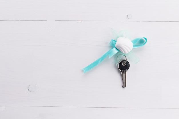 Silberne schlüssel mit blauem band und muschel