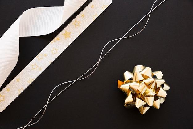 Silberne schnur; weiß- und sternformband und goldener bogen auf schwarzem hintergrund
