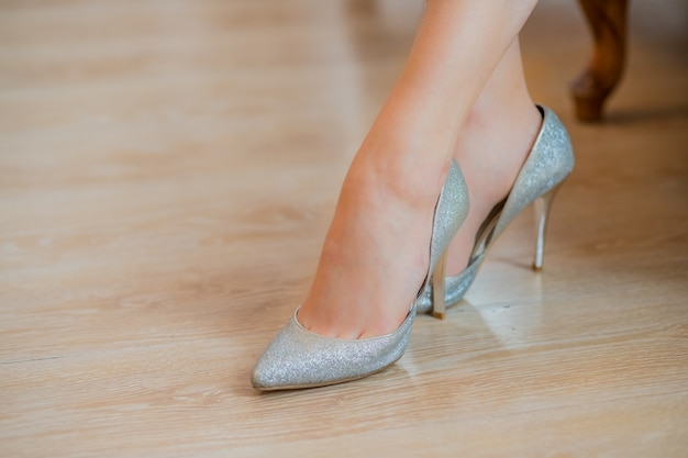 Silberne schuhe mit hohen absätzen. füße in silbernen luxus-damenschuhen. stilvolle hausschuhe.