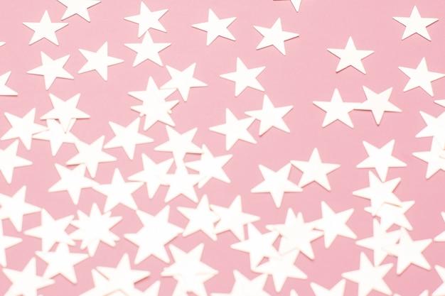 Silberne sterne auf rosafarbener oberfläche