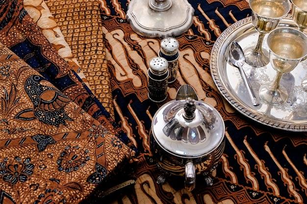 Silberne teekanne, silberglassatz, silberner löffel mit batik-gewebe-hintergrund