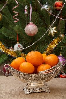Silberne vase mit orangen auf sackleinen und weihnachtsbaum mit spielzeugbällen und girlanden im hintergrund.