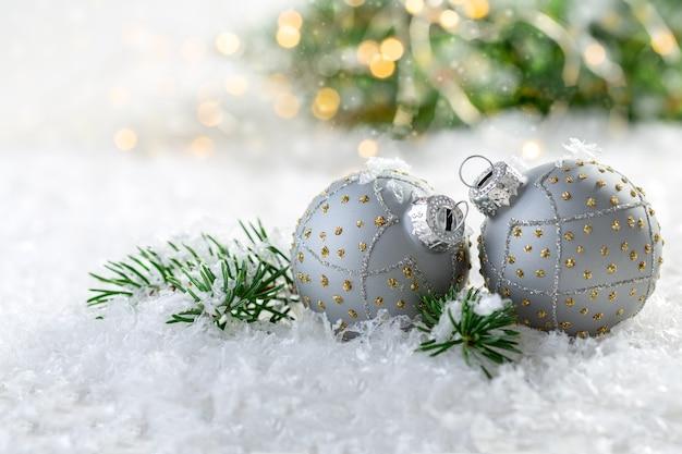 Silberne weihnachtsballons auf einem schneebedeckten tisch