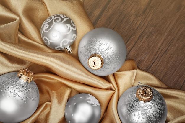 Silberne weihnachtskugeln auf beige seidigem hintergrund