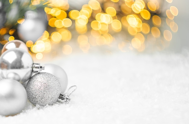 Silberne weihnachtskugeln, die auf dem schnee auf dem hintergrund des weihnachtsbaumes liegen