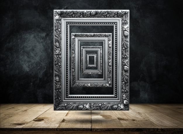 Silberner antiker bilderrahmen auf dunkler schmutzwand mit der holztischspitze mysteriös, verwirrt, hintergrund