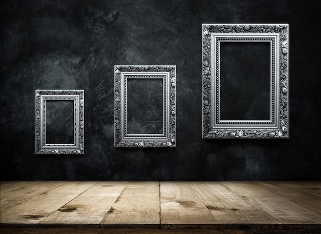 Silberner antiker bilderrahmen auf dunkler schmutzwand mit hölzerner tischplatte