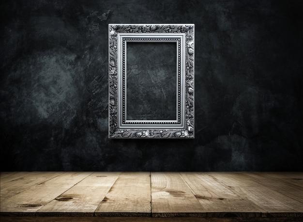Silberner antiker foto rahmen auf dunklen schmutzwandhintergrund mit der holztischoberseite