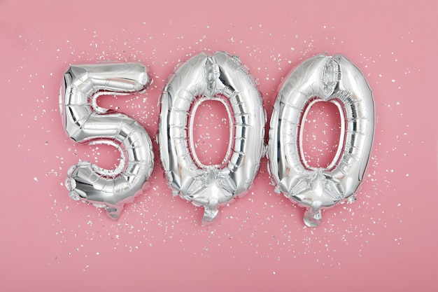 Silberner ballon mit nummer auf rosa hintergrund
