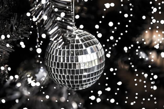 Silberner glänzender disco-spielzeugball am weihnachtsbaum mit schnee. urlaubskonzept. nahaufnahme.