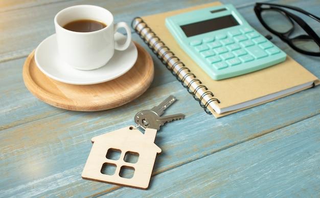 Silberner hausschlüssel, der auf hölzernem tablett, leasing, versicherung oder hypothek in einem immobilienkonzept liegt, betrachtet niedrigen winkel mit fokus auf die spitze.