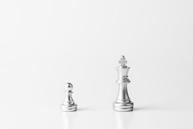 Silberner könig und bauernschach stehen auf dem weißen schreibtisch.